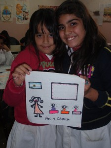 Two female students smiling and holding a quilt square with a pictures of a classroom drawn on it.